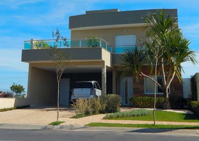 As platibandas sobre os beirais na fachada desta casa compõem linhas suavemente curvadas. A laje sobre a garagem é um grande terraço da suíte do casal.