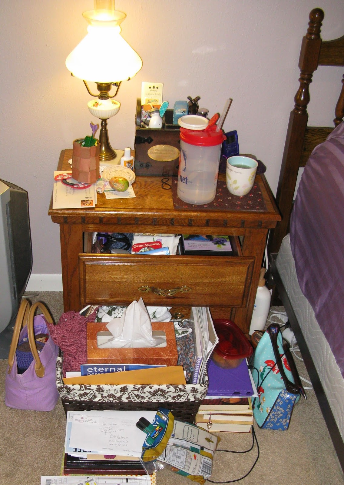 a messy nightstand and bedside
