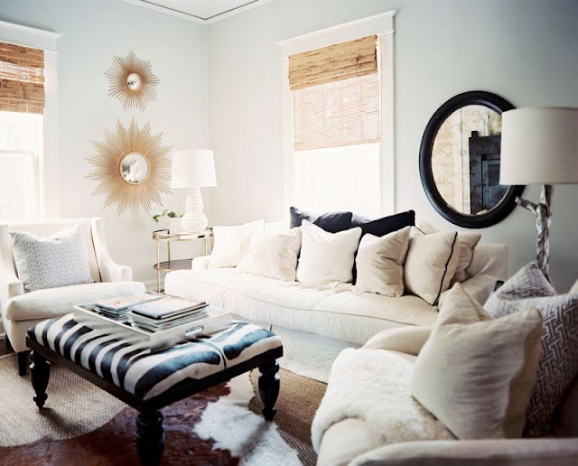 modern living room with white sofa, dueling armchairs, a zebra print upholstered ottoman with dark wood legs and a white gourd lamp