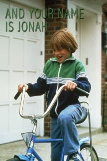 The cover art for And Your Name is Jonah, showing the title character riding his bicycle down the road.