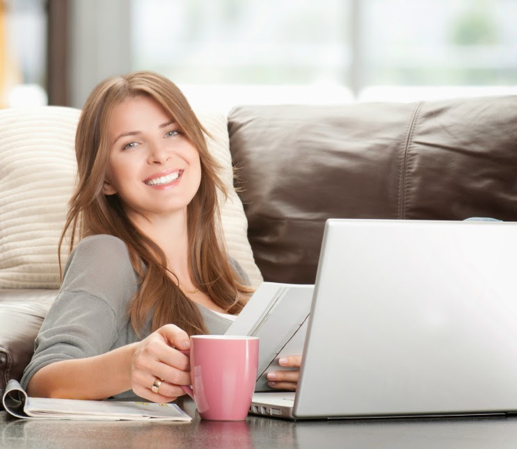 Woman smiling and sitting in front of her laptop computer.