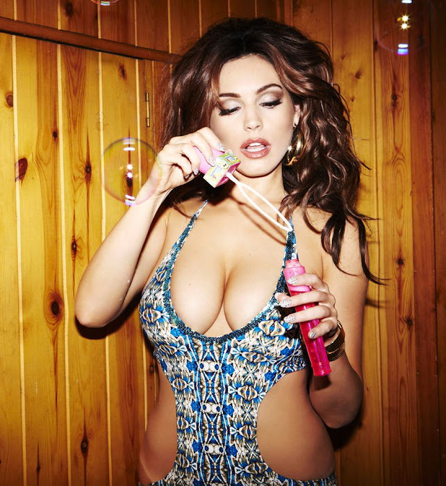 Kelly Brook in one piece swimsuit blowing bubbles