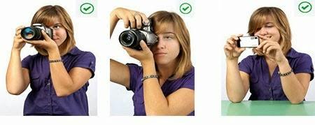 Memegang kamera dengan dua tangan