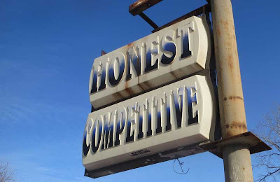 Lit plastic sign, faded by sun, with two words: HONEST COMPETITIVE