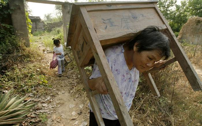 A woman carries a desk while a young girl carries a chair to school in Macheng, Hubei province, China, where primary school pupils have to bring their own desks and chairsPicture: Imaginechina / Rex Features