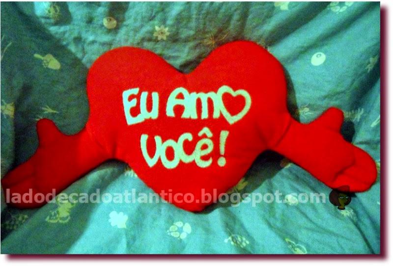 """Foto de uma almofada vermelha em forma de coração com braços, com a frase """"Eu Amo Você!"""""""