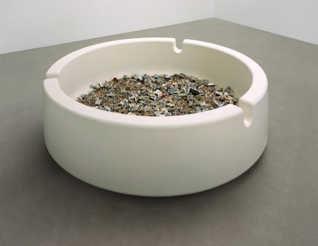A giant white ashtray full of cigarette packets and ash