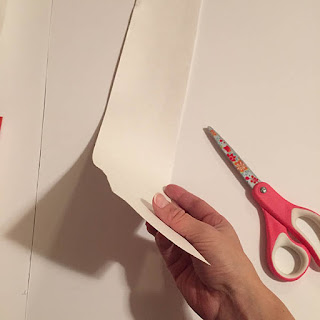Cutting strips of white poster board with pink scissors