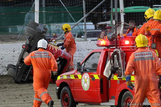 RaceSafe fire crew run to the aid of Sam Bartholomew in the first heat of the Superstocks at the grand opening of Meeanee Speedway, Meeanee, Napier. photograph