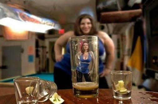 Chica gorda se ve delgada y atractiva a través de un vaso de cerveza.
