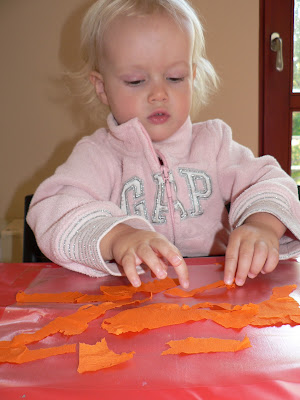 young child making a tissue paper sun catcher craft