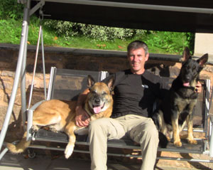 Two german shepherd sat in a louger swing with Paul in the middle