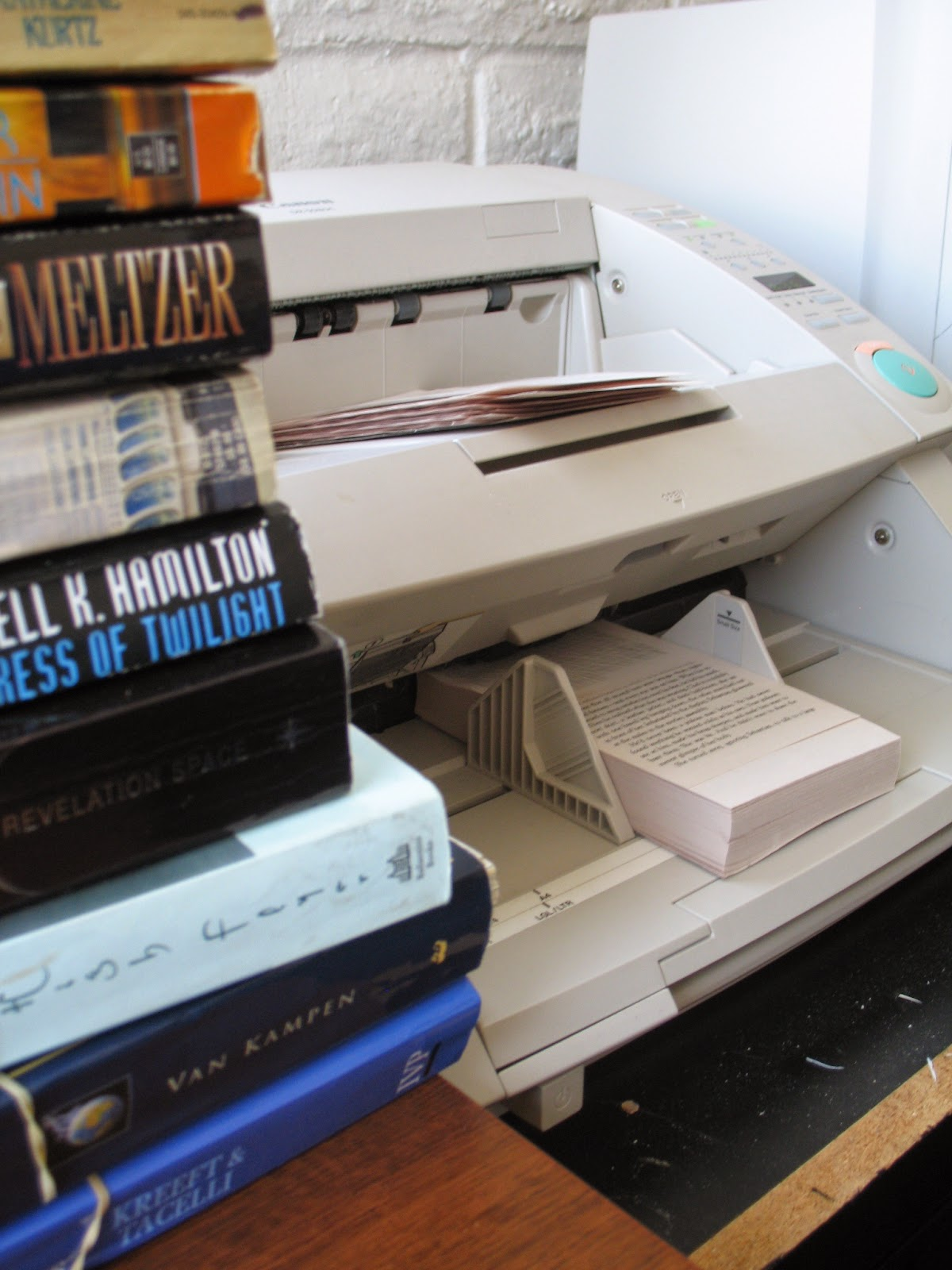 A pile of unbound books on a desk, adjacent to a scanner, with a chopped book being scanned.
