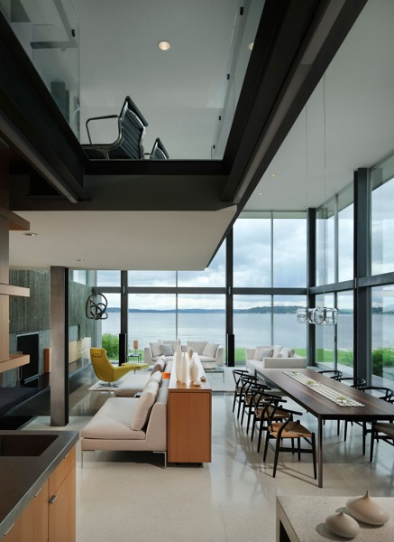 Picture of modern dining room on the ground floor and working desk on the upper floor as seen through the glass floor