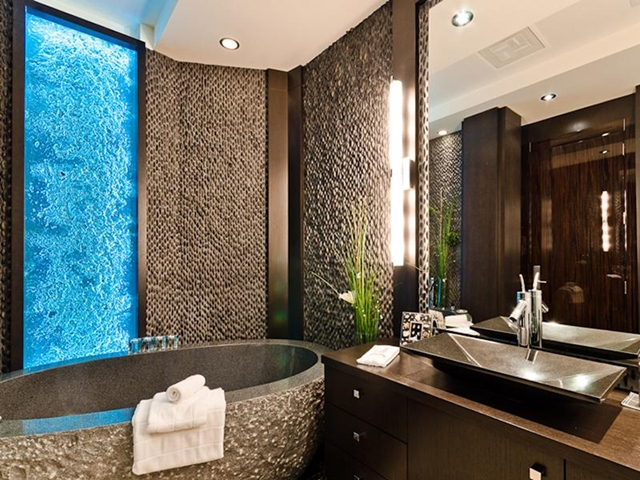 Picture of modern dark stone bathtub by the stone wall in the luxury modern bathroom