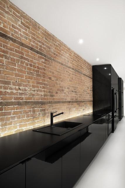 Cuisine avec façade stratifié noir brillant, plan de travail fin noir, évier noir et mitigeur noir.