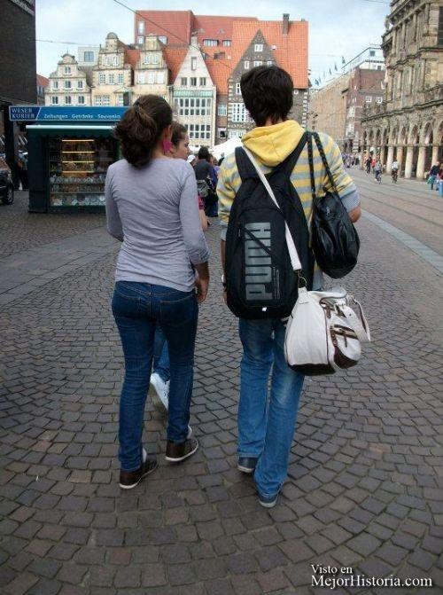 Chico lleva varias bolsos y mochilas a chica.