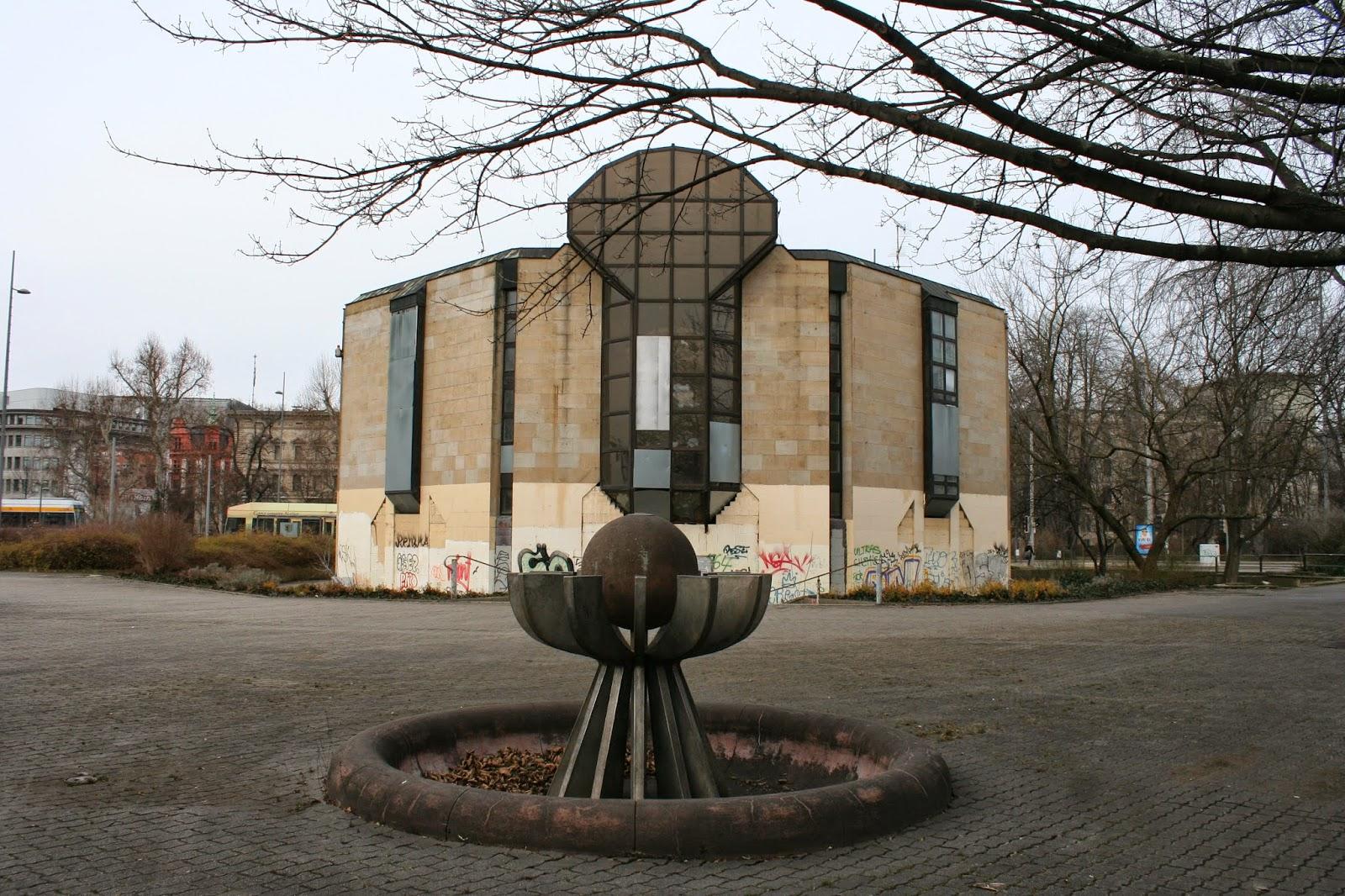 """Wir reden hier von einem technischen Denkmal und vom ehemaligen """"Bowlingtreff"""" am Wilhelm-Leuschner-Platz, doch eigentlich wurde das Eingangsbauwerk nur aufgesetzt, da dort schon seit Jahren ein unterirdisches Strom-Umspannwerk der Stadt Leipzig vorhanden war - hier dmit dem Brunnen vor dem Haus"""