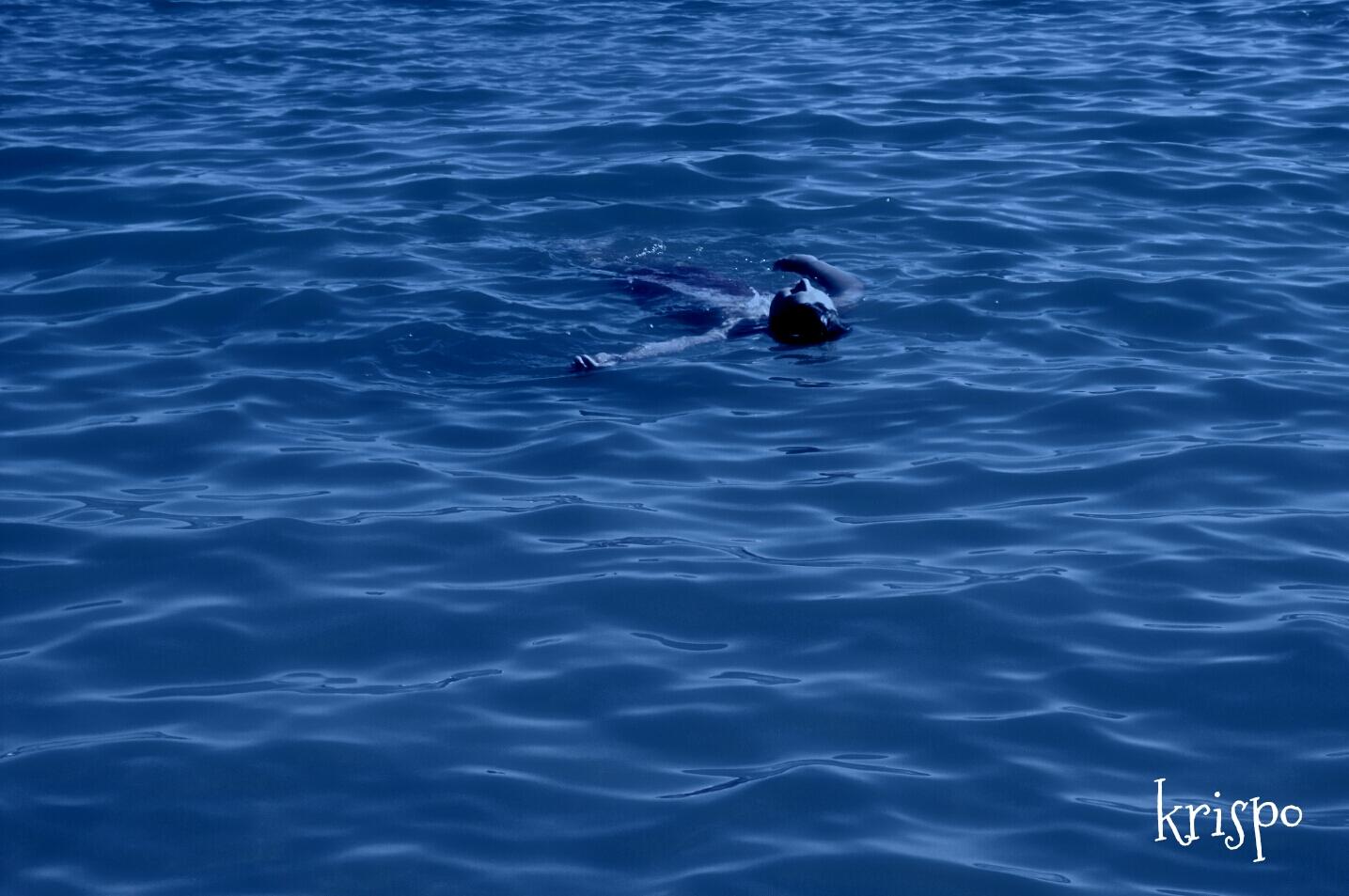 niño flotando boca arriba en mar por la noche