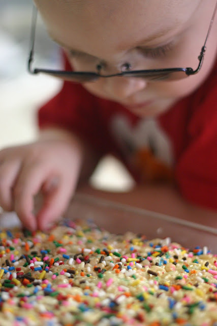 Child picking sprinkles off yummy treats