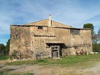 La façana de llevant del Mas de les Claperoses, on destaca una premsa de vi que s'ha conservat com a motiu decoratiu