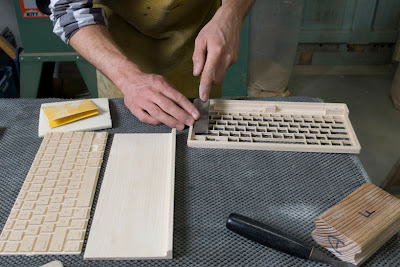keyboard in three pieces and workman using chisel on one piece