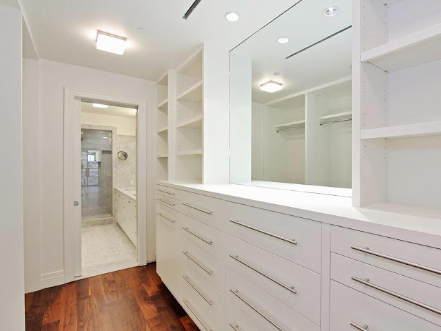 Walk in closet/dressing room with white cabinets and drawers with long silver drawer pulls and a wood floor