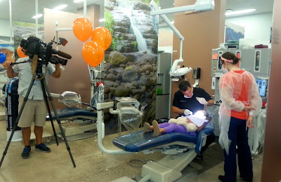 photo from dental clinic. Volunteer staff and students providing care to child while KPHO photographer videotapes the procedure.