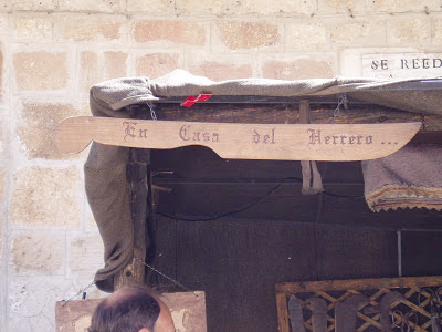 """En un puesto de feria se ve escrito sobre un gran cuchillo de madera """"En casa del herrero..."""""""