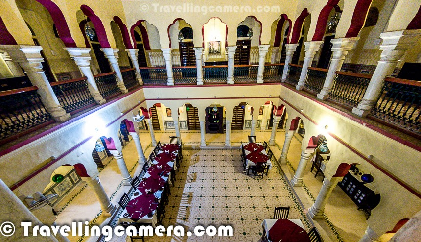 For last few weeks, you must be seeing various interesting things to explore around Churu region of Rajasthan. During our weekend trip to Churu, we stayed at Malji ka Kamara which is located in the middle of Churu town and this property was a Haveli of Kotharis and now converted into a Heritage Hotel. This Photo Journey shares some of the photographs from Malji Ka Kamara and some details about The Hotel, services they offer and relevant stuff. After a tiring drive from Delhi to Churu, we reached Malji Ka Kamara which is located in one of the streets near Churu Market. Ater reaching at the place, we parked our car. There is space for parking 5-6 vehicles inside the campus and few outside in the street. So Parking can be an issue is Hotel has decent bookings. But the good part is that many of the folks come to Churu by Trains, so it's highly likely that you will get parking inside the campus. Anyways, staff helped us in taking the luggage to our room and offered a welcome drink.Malji Ka Kamra has Solar heating system to get hot water which effectively means that in morning, one may need to wait for hot water. But if needed, staff provides hot water in rooms. Malji Ka Kamra has installed geyser in two of the rooms on top floor and we were lucky to have one of them, so more freedom in getting Hot water whenever we wanted :) , although the fitting were wrong.. The Cold point was giving hot water :) ... After having bath with hot water and a quick nap, we headed towards the restaurant for lunch.Above Photograph shows the Restaurant of Malji Ka Kamara and the view is from first floor. Like the Havelis we see in Bollywood movies, Malji Ka Kamra has very high roof in the middle and first floor of the Haveli ha visibility to the ground floor through lobbies in all four directions. This corridor gives a royal feeling of being at a haveli. Some parts of the Haveli are kept intact to make visitors feel about the older look and feel of the place. It seems Foreigner tourists like that style, which don't even understood by Indian visitors. This is a common sentence you would hear or experience in Rajasthan. Folks from Rajasthan Tourism industry understand the foreigner tourists better and plan things accordingly. Let me stop here and write a separate post of the behavioral and strategic decision making of Rajasthan Tourism Stakeholders.Malji ka Kamra was built long time back in 1920, which was use by Kotharis for many years and then turned into ruins for a significant duration. Restoration of this Haveli started in 2006.. Haveli was in very bad shape when restoration started, because it was locked for more than 20 years and condition was very bad, which is happening with many of the other Havelis in Churu. Kotharis used to have this Haveli only for guests. Their family Haveli is just across the street which was again a huge building with colorful paintings. Malji Ka Kamara has mint green extiriors and there are different personalities sculptured on the walls, although these creations look very odd :) . It seems that original color of the Haveli was almost same and restorers attempted to retain those hues of this building.ere is view we get on seeing up from the Restaurant of Malji Ka Kamara.Malji Ka Kamara is considered as one of the well maintained Havelis (palaces) in Shekhawati region of Rajasthan State in India.Food served at Malji Ka kamara was nice. The Hotel has trained local chefs who are really good at cooking Rajasthani as well as other cuisines. During our stay we were were some of the famous rajasthani delicacies and we loved them. Staff was very polite, although they may need more training with time. The good part is the local folks are hired by Hotel which is a good way of ensuring that local communities also grow along with local tourism and the business of these Hotels. Local folks may not be that trained but with time, things can be changed and we have seen that happening in many of the other properties across India. So I personally like such properties which take responsibility of their own localities one or the other way.The Staff at Malji Ka Kamara offers some of the cool activities which make your stay experience more memorable to cherish for longer period of time. Two days for me were very tight and I wish to visit Churu again with at least 3 days in hands. I love to spend time with local culture, place, people at my own pace. During the stay we had Heritage Haveli Walk in Churu Town, Desert BonFire with lot of shooting stars around us, High Tea at Sethani ka Joahara, Visit to Golden Jain Temple in Churu Town, Royal Lunch at Prem Sarovar, Haveli Tour in Ramgarh, Visit to another Heritage Hotel in Ramgarh, Meeting National Award Winner Family of Wood-Carving Artists and some shopping of hand-made lacquer bangels. This list is never-ending and we missed lot of things which will be covered during our next visit. And here I would like to thanks the staff at Malji Ka Kamara who arranged all of these for us. Churu is not very popular destination among majority of the tourists who visit Rajasthan State of India, but it's definitely a hot off-beat destination and many of the foreigner tourists visit Shekhawati region and Thar Desert. Churu which is gateway to Thar is another special destination for those visitors. Due to seasonal and lesser inflow of tourists, local hospitality industry is not that mature but that gels well with the local atmosphere. So if you plan to visit this region, expect some hiccups and some non-touristic things.Above photograph shows one of the few rooms which are in their original form. But there are only very few such rooms which are maintained like they were earlier and reason is that it was very difficult to restore major parts of the Haveli. Arrangements in all the rooms are quite comfortable and if you feel something missing, staff is ready to help you on a call. Staff at Malji Ka Kamara is quite co-operative. Some of them had some language problems, but it was manageable. This Hotel has some of the selected folks from the region like Mr. Lal Singh, who is acclaimed guide in Shekhawati region. He took us to the Haveli tour in Churu. Since most of the Haveli Owners/Caretakers know him, we got access to go inside and see some of the beautiful Havelis in town. Likewise, Malaji Ka Kamara is associated with some historians who visit the hotel to share some facts about the history of Churu and Shekhawati with tourists staying there. Although we had our own doubts on some of the facts shared by Mr. Bhanwar Singh Somour, but he looked a passionate and knowledgeable person who has high regards for his land, culture and the way different families of this region has influenced various things in our country.Most of the rooms at Malji Ka Kamra look just like any other Hotel and don't have any old paintings on walls of roof, expect the few which are mentioned above. But Malji Ka Kamra Management tried to give Rajasthani touch to the rooms by using some of the local crafted stuff. The rooms are large and comfortable with basic facilities and bathrooms are also very basic. To know more about the place, checkout their original website which has appropriate contact details as well.We enjoyed being there at Malji Ka Kamara, it's humble staff and moderatelycrowded lanes full of old Havelis around it...