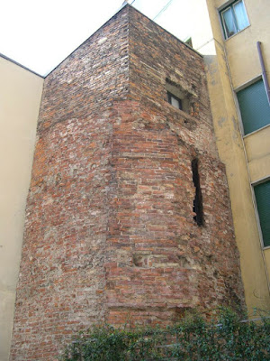 remaining Roman tower that formed part of Porta Ticinese shown embedded into the walls of two adjoining buildings in Largo Carrobbio, Milan