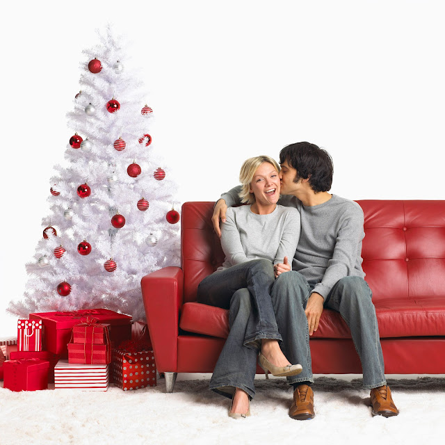 A young, happy couple sitting on red leather couch in front of a white Christmas tree.