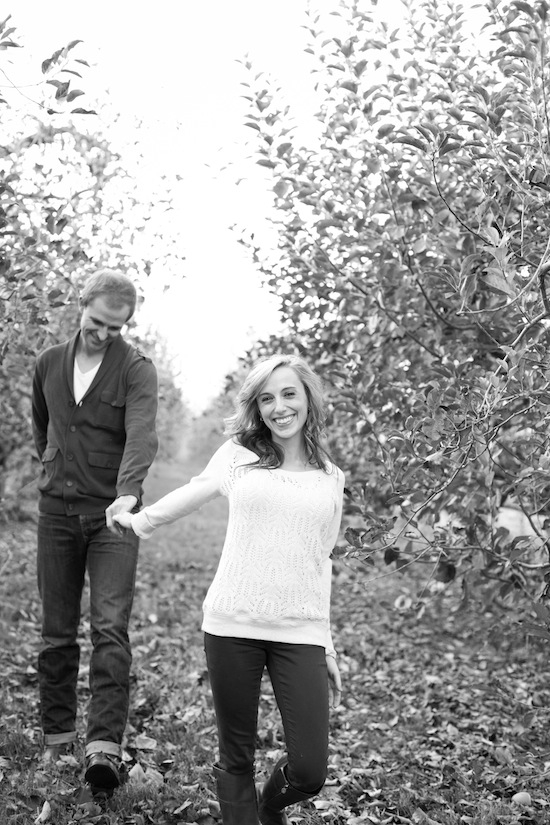 couple strolling through an orchard during their engagement session