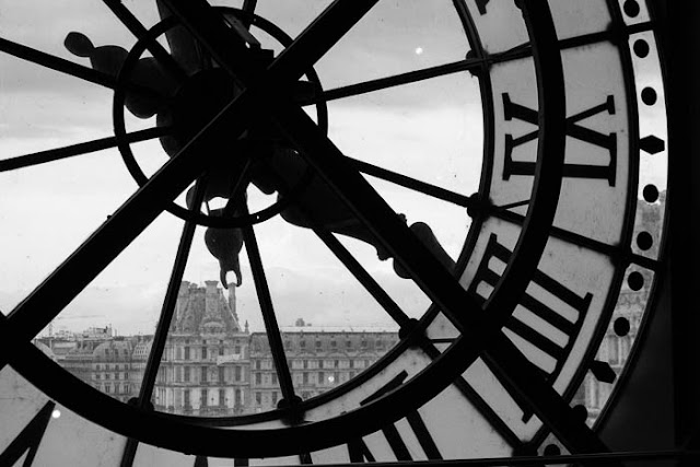 view of the Louvre through the window clock at Musee d'Orsay
