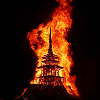 pointy wooden tower burning at night