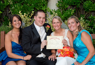 Jillian and Andrew sit outside The Canal with their sisters, holding their marriage certificate