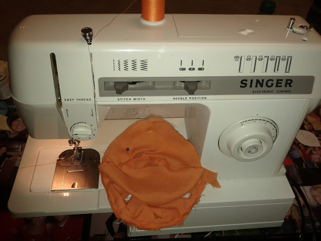 The final stitches are been machine sewn into the orange ball.  Some white and black pins stick out from the orange fabric.