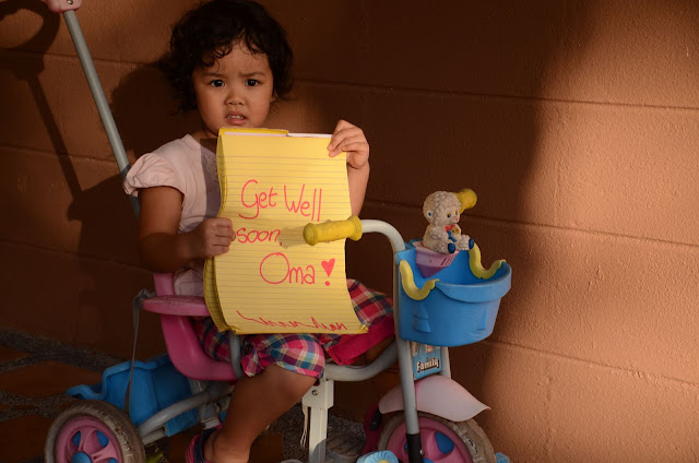 Kecil holding yellow pad with writing: Get well soon, Oma!