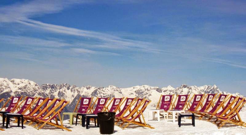 Deckchairs lined up in the snow with blue skies