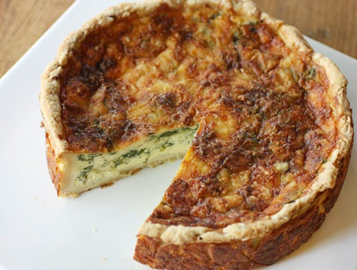 lisa is cooking classic french quiche with spinach and leeks