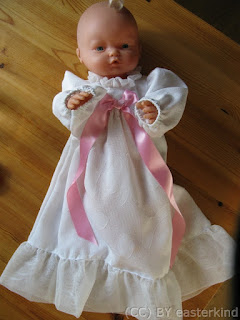 baby doll, wearing long white gown with long pink ribbon decoration