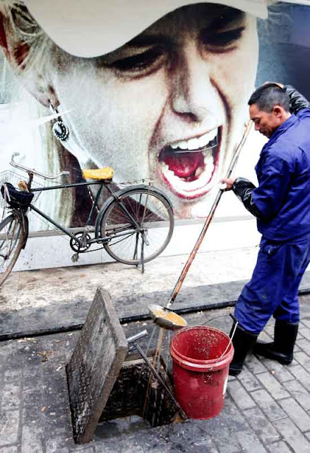 A man collects oil floating in sewage