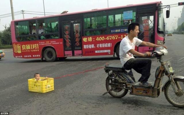 Chinês é flagrado rebocando criança numa motoneta