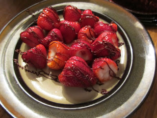 a plate full of ripe strawberries drizzled with chocolate
