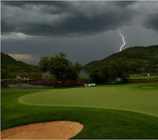 Photo of golf course green and sand trap with a cloudy sky and lightning on the background