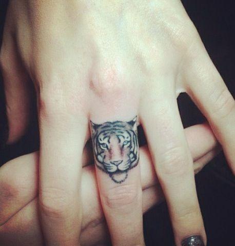 chica con el dedo medio tatuado con un tigre de bengala