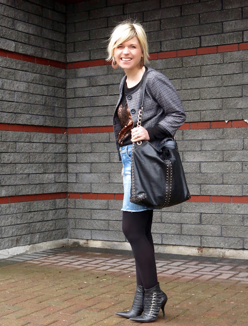 styling a denim cut-off skirt with a sequinned sweater, Chanel-inspired jacket, black tights, and bebe booties