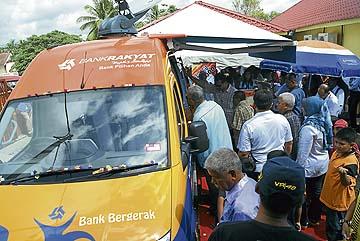 Orang ramai melihat perkhidmatan bank bergerak yang dirasmikan Ismail Sabri di FELDA Bukit Mendi.
