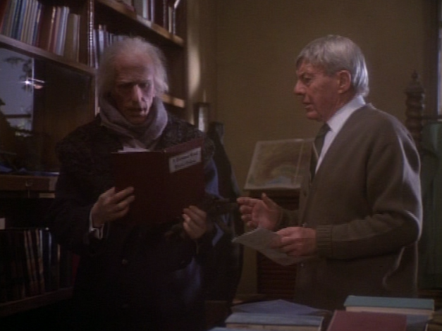 slade with the shop owner david wayne examining a first edition of dickens christmas carol