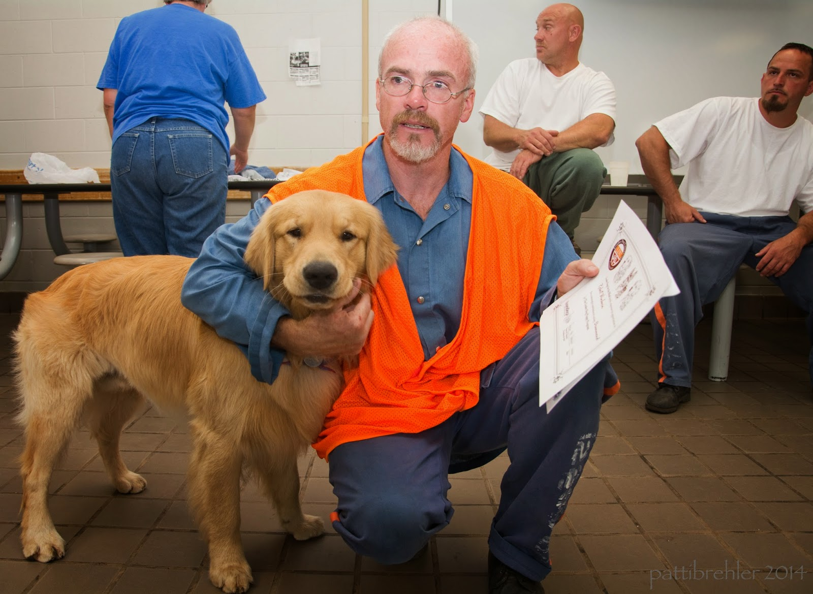 A man dressed in the priosn blue uniform and an orange vest is squatting down with a golden retriever on the left. The man's right arm is wrapped around the shoulders of the dog. The dog is standing and looking at the camera. The man is holding a certificate in his left hand. There is a woman and two men in the background.